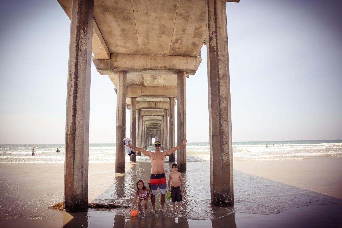 family under the beach pier