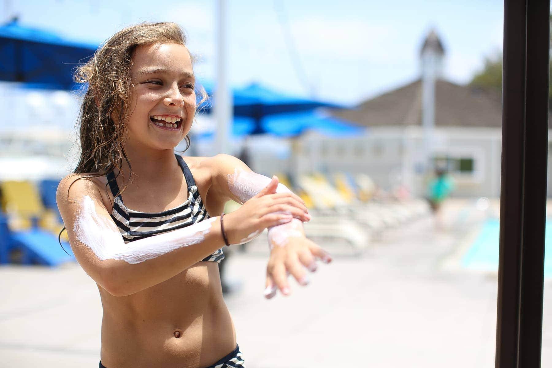 girl putting on sunblock