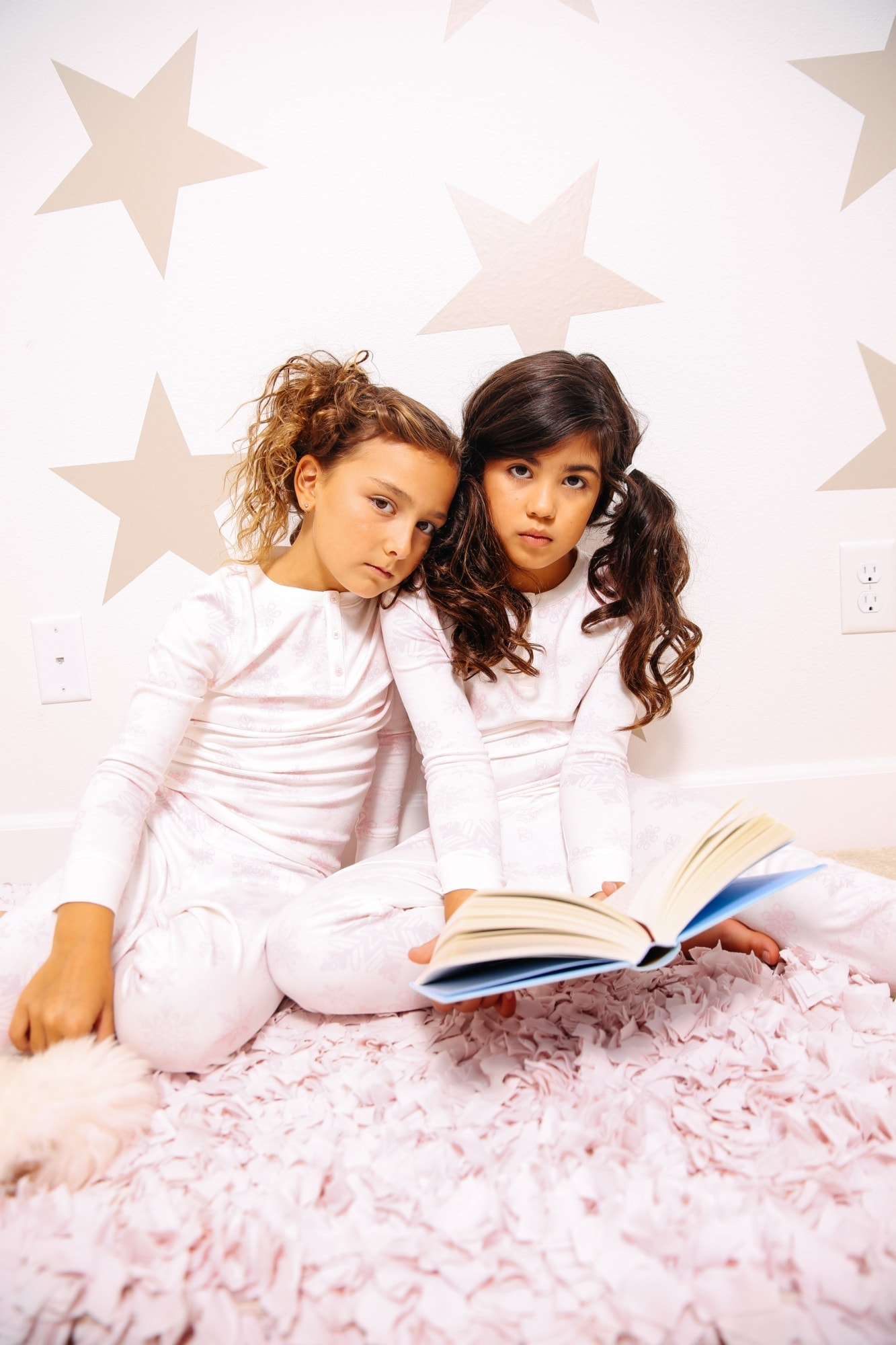 girls in pajamas reading a book