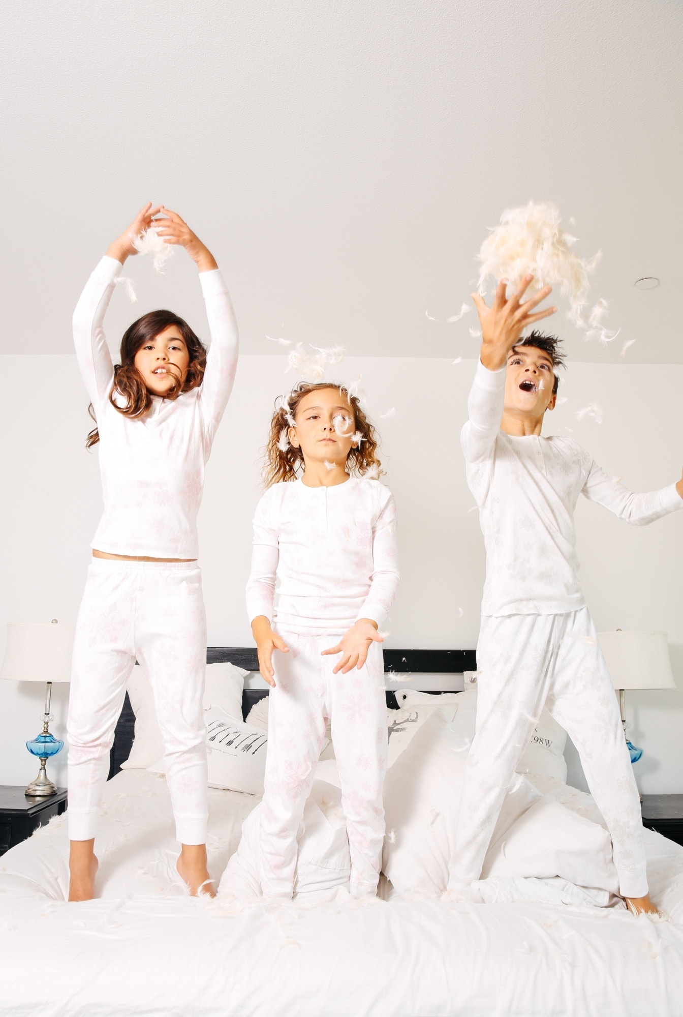 kids jumping on bed with feathers
