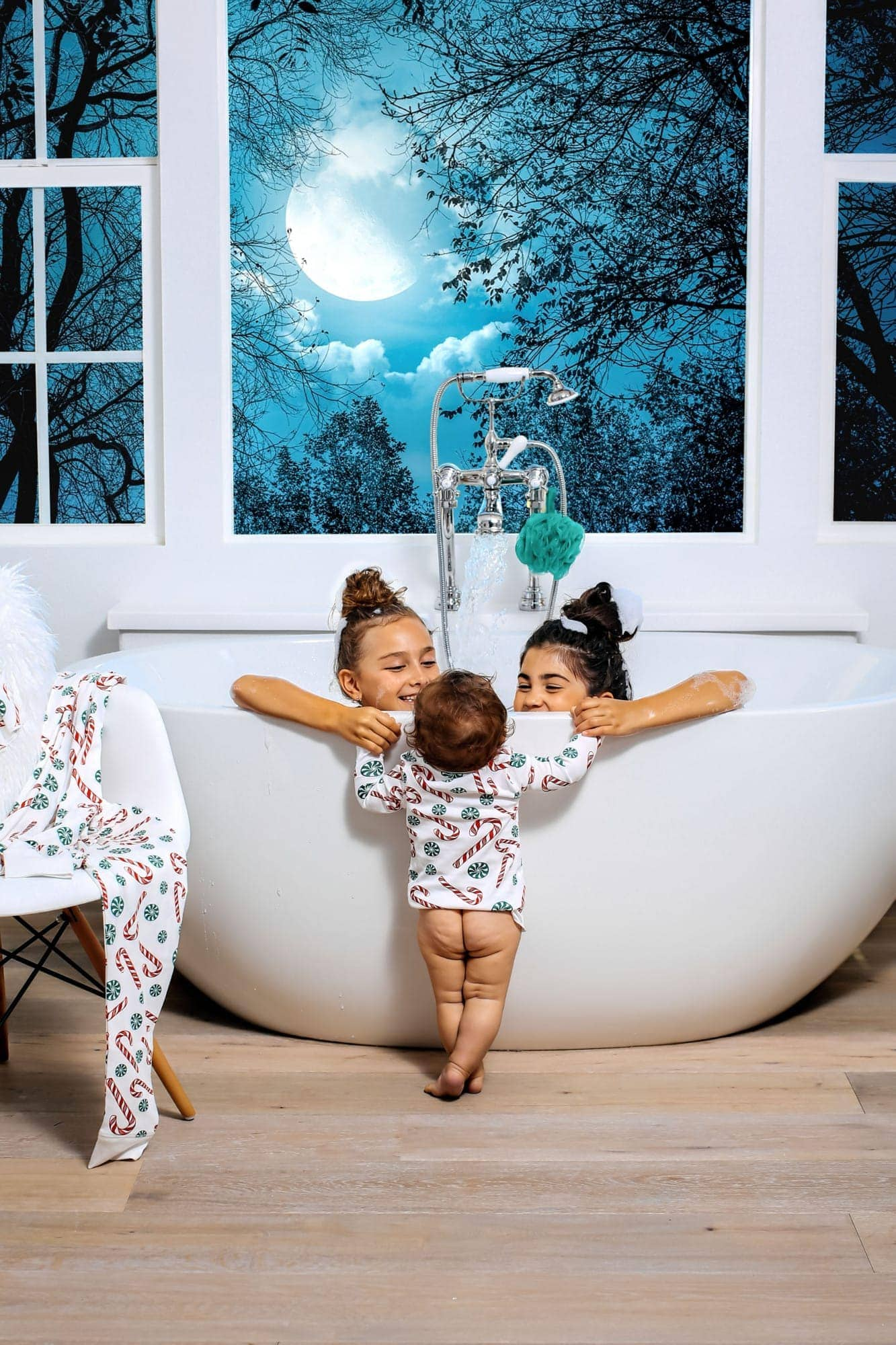 girls in bathtub with baby standing
