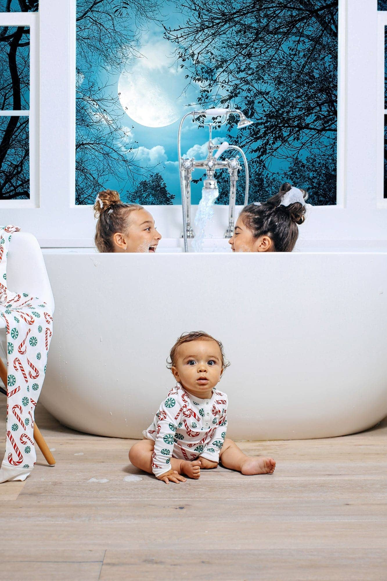 girls in bathtub with baby sitting outside