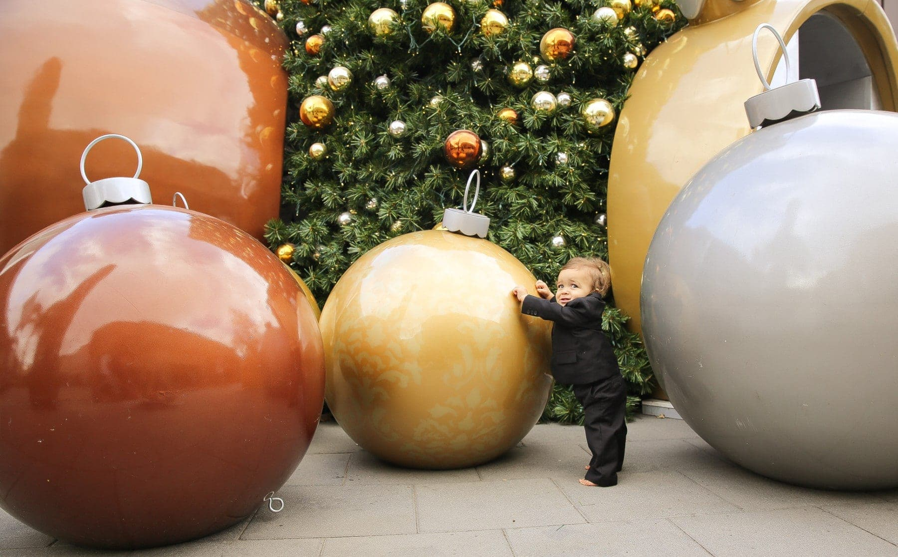 baby playing in giant christmas ornaments