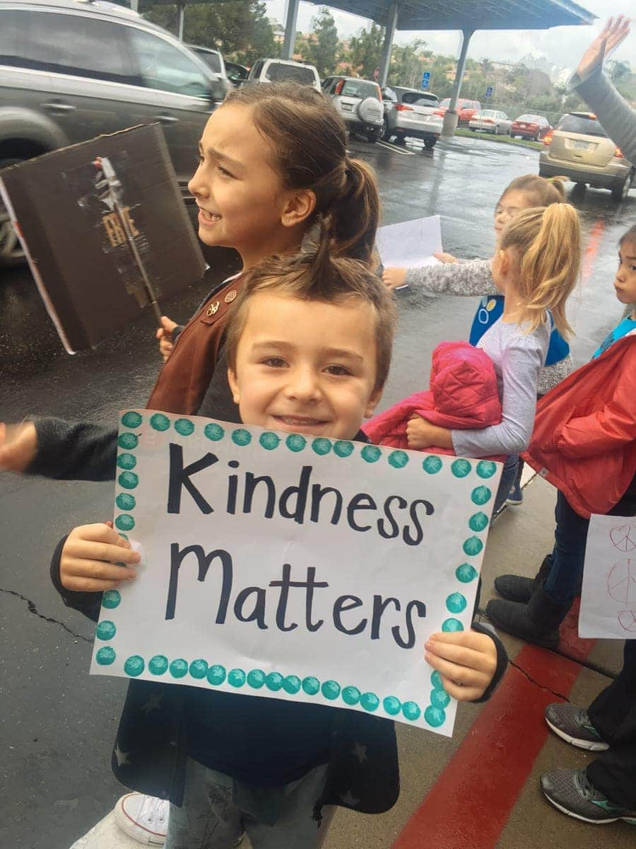 boy holding kindness matters sign