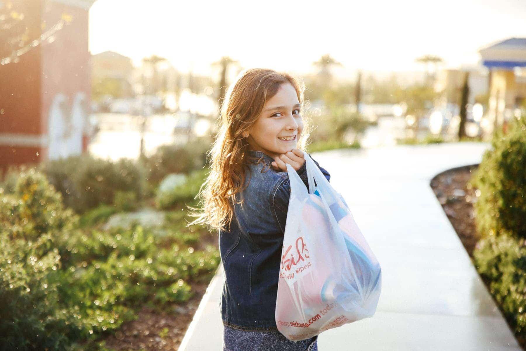 girl walking down sidewalk with bag