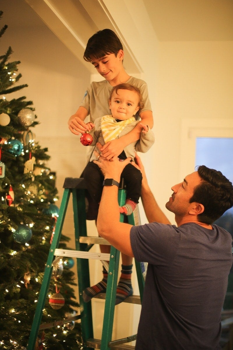 father and sons decorating christmas tree