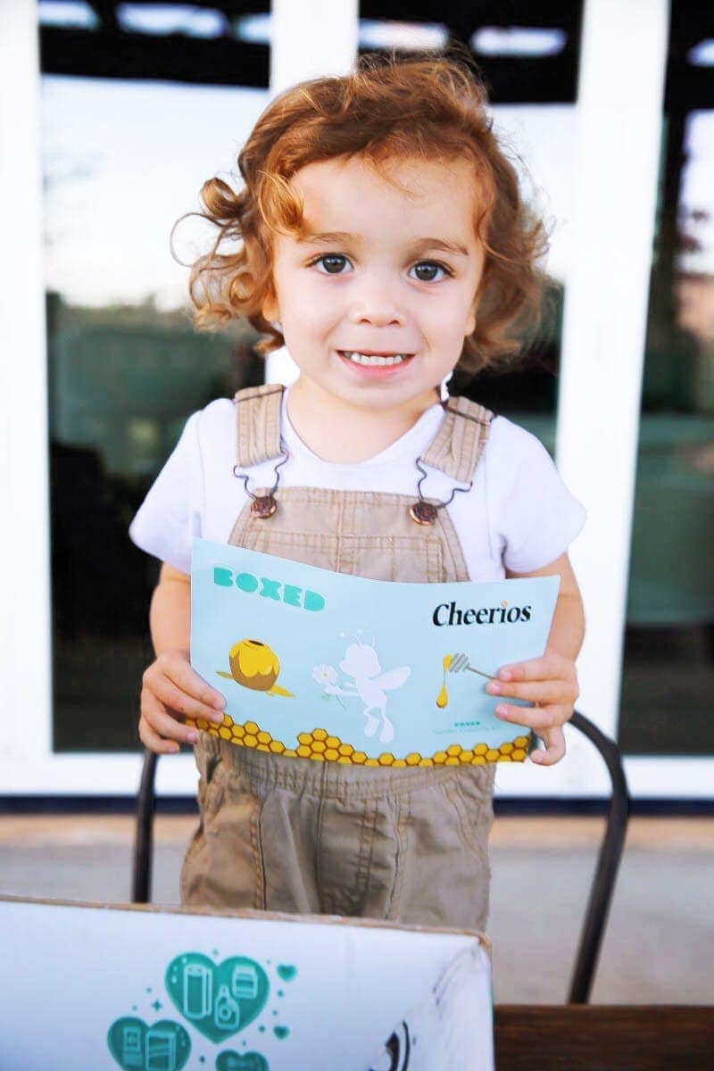 Child holding stickers from the Boxed and General Mills Bring Back the Bees campaign creativity kit