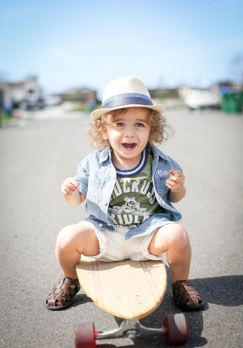 toddler on skateboard with hat