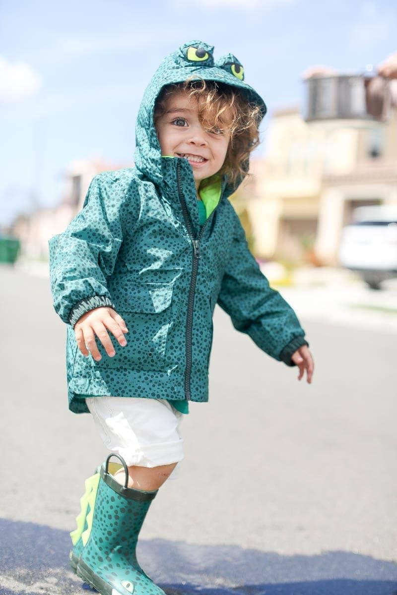 happy boy in raincoat and rain boots