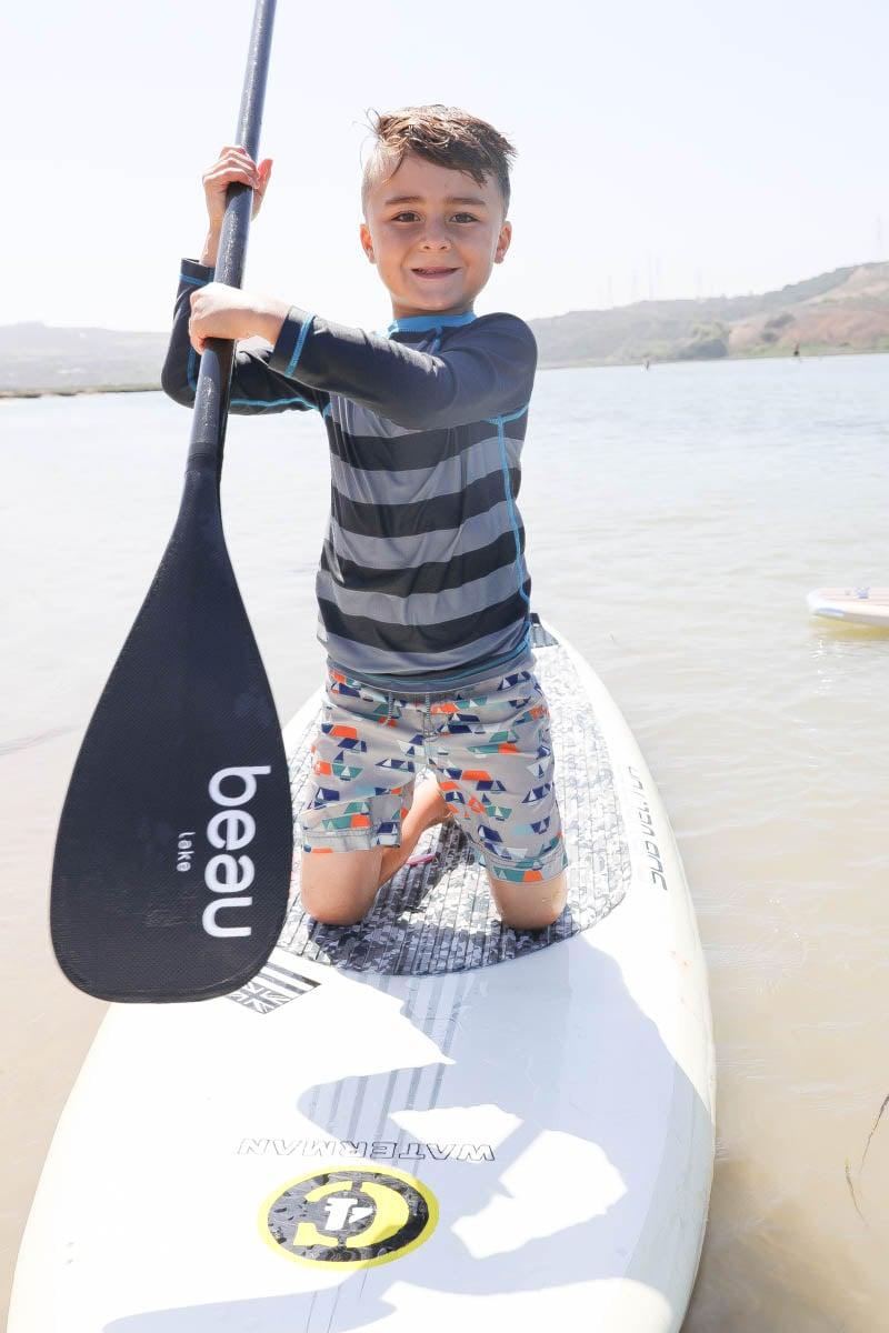 Kid Smiling While on Paddle Board #familytravelsandiego #sandiego #fourseasonsresidenceclub #bigfamilytravel