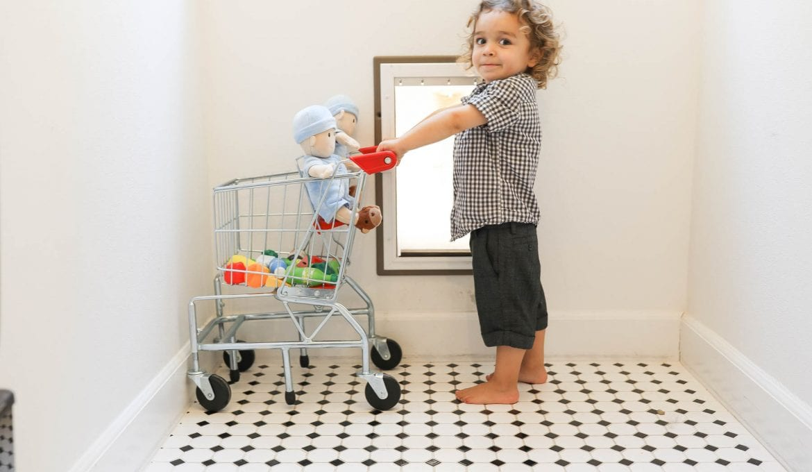 boy pushing cart with baby dolls