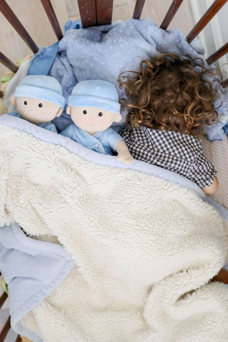 Kid Sleeping with Baby Dolls