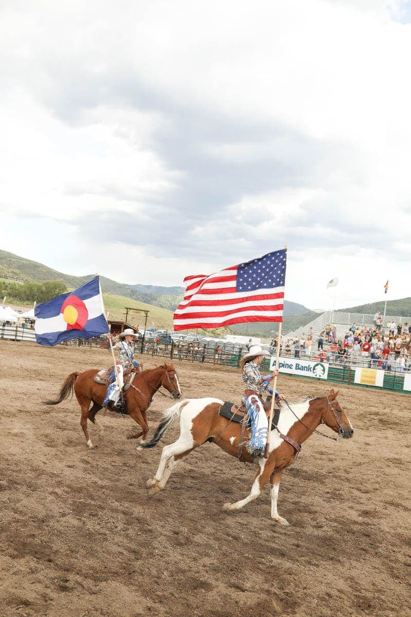 cowgirls holding flags #summer #vailcolorado #vacation #citygirlgonemom