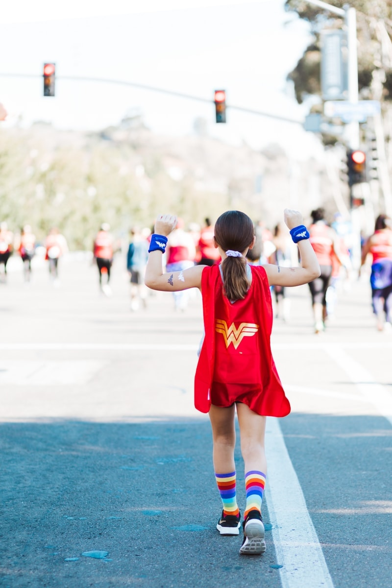 girl wearing supergirl cape and headaches