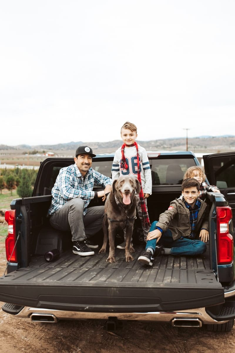 family and dog in the back of a truck