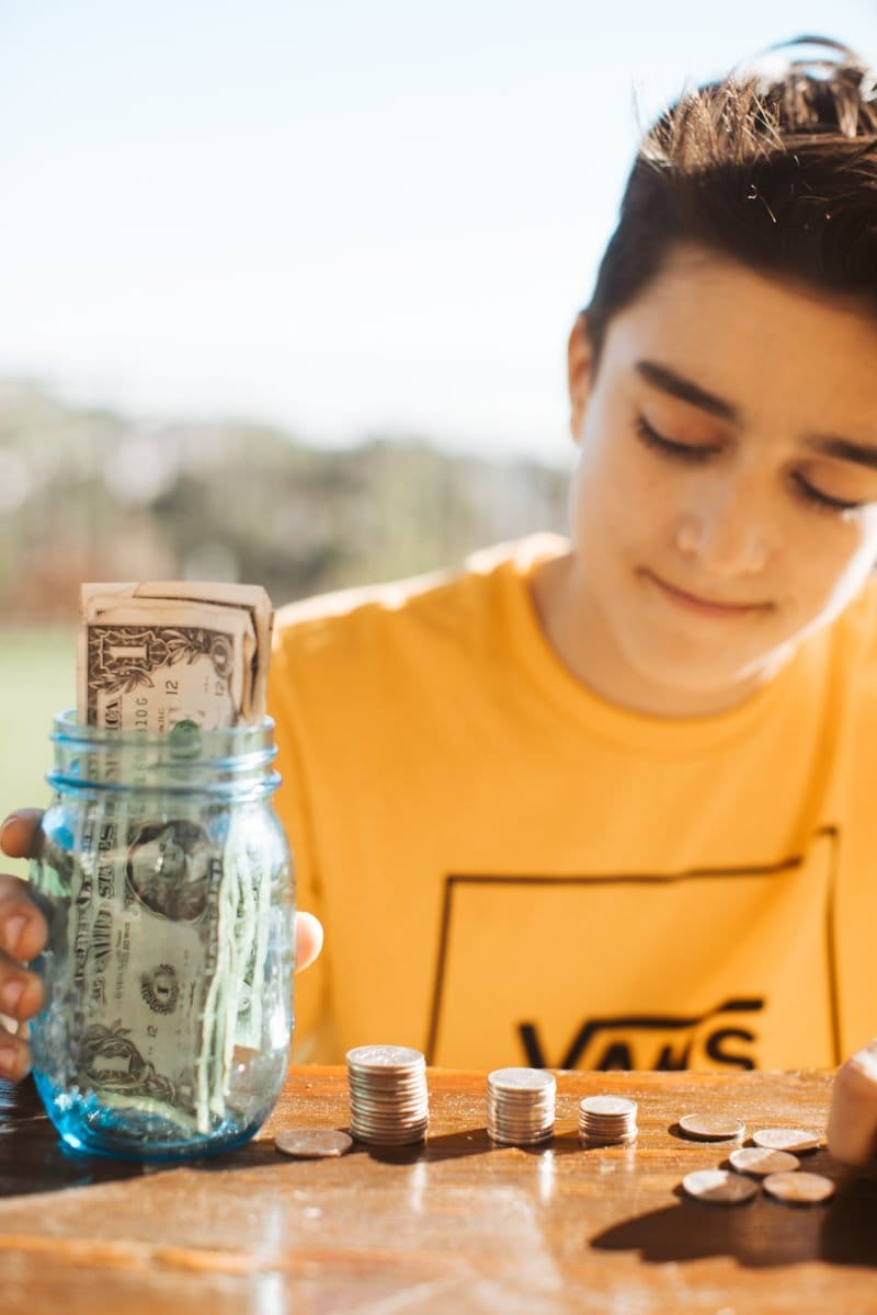 boy counting money in jar