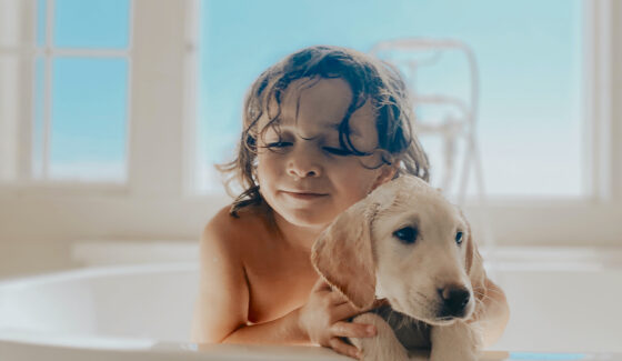 toddler and puppy in bathtub
