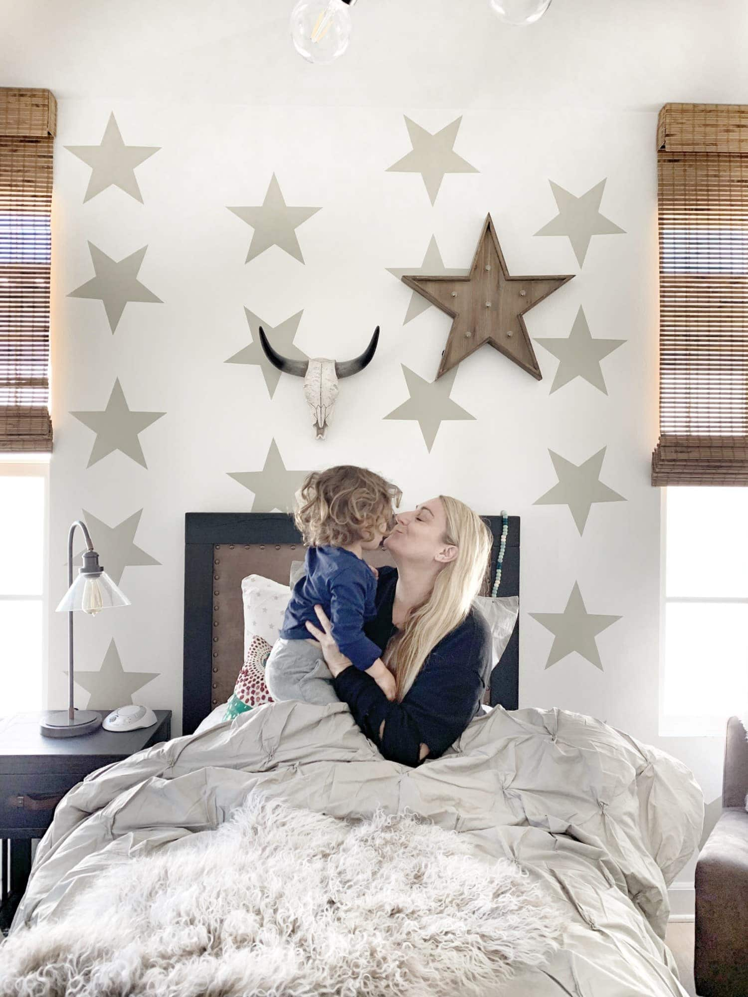 mom kissing her toddler in bed