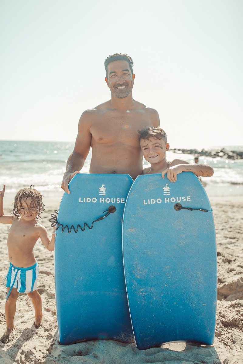 father and sons at beach with boogie boards