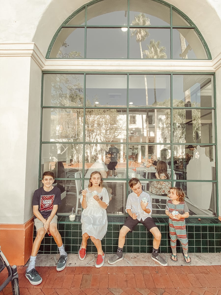 kids sitting outside a store