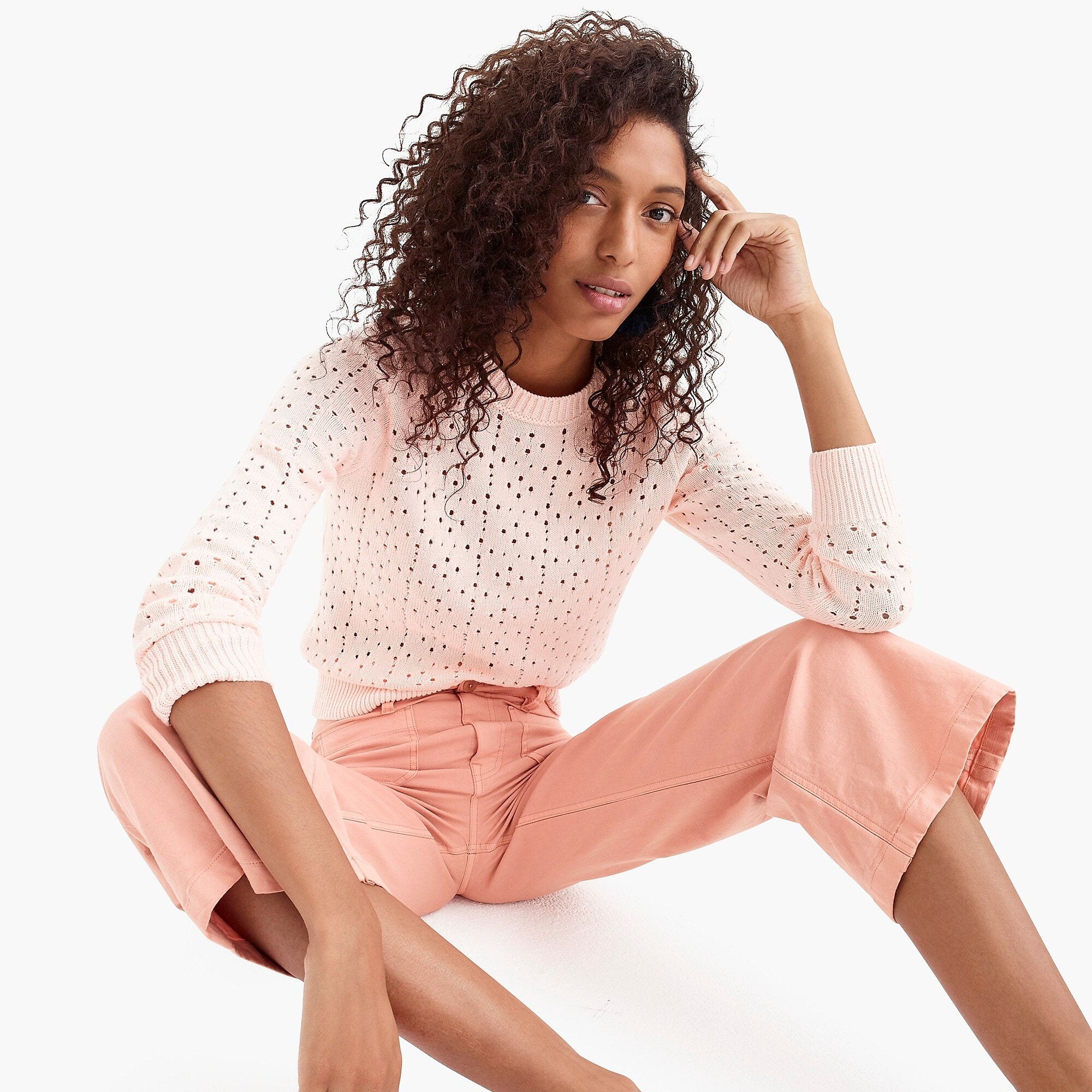 woman sitting in pink sweater