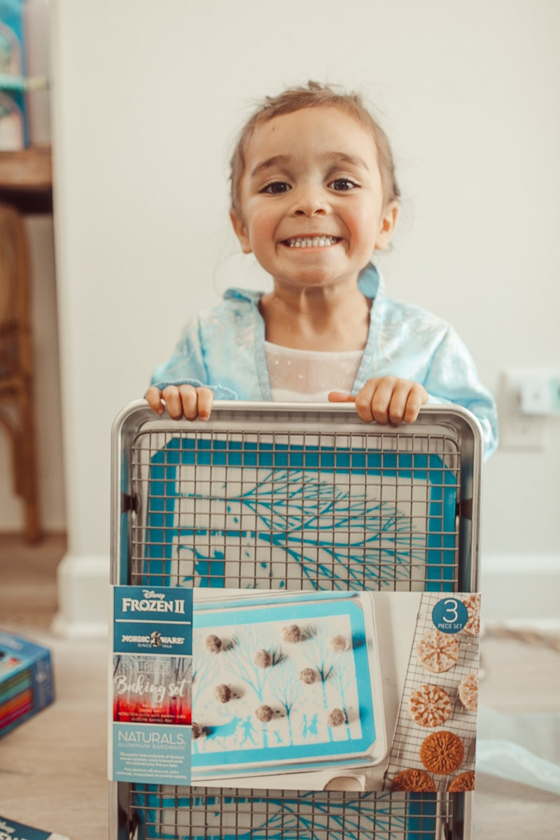 toddler with disney frozen baking sheet