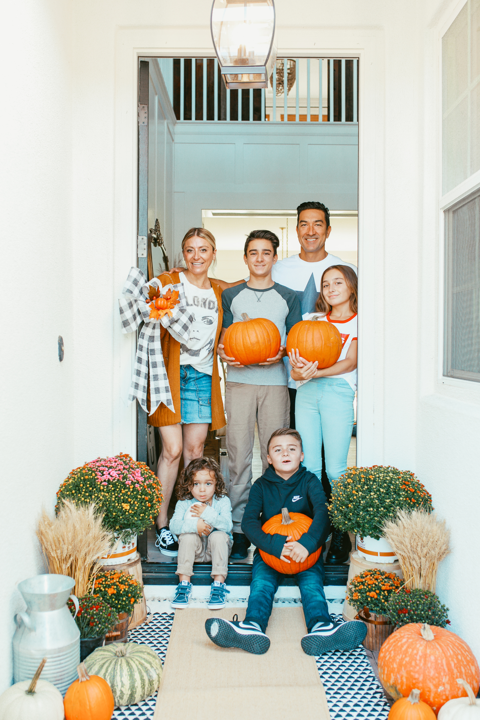 family holding pumpkins