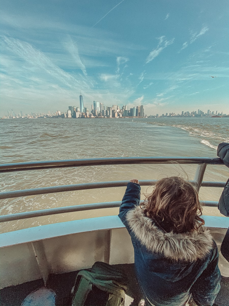 toddler on boat with new york city skyline
