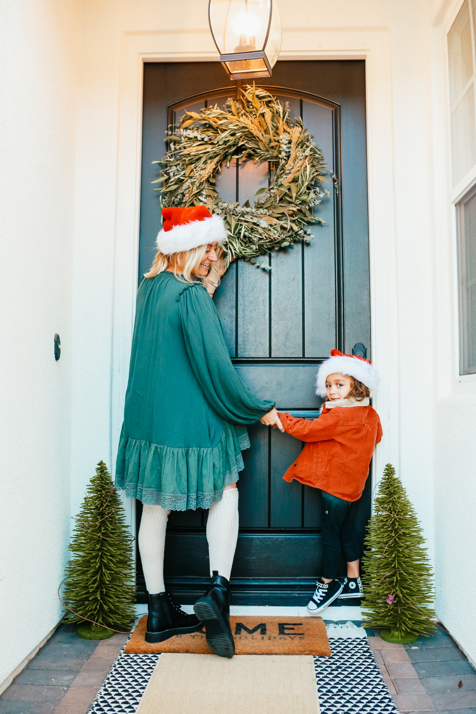 mom and toddler putting up wreath
