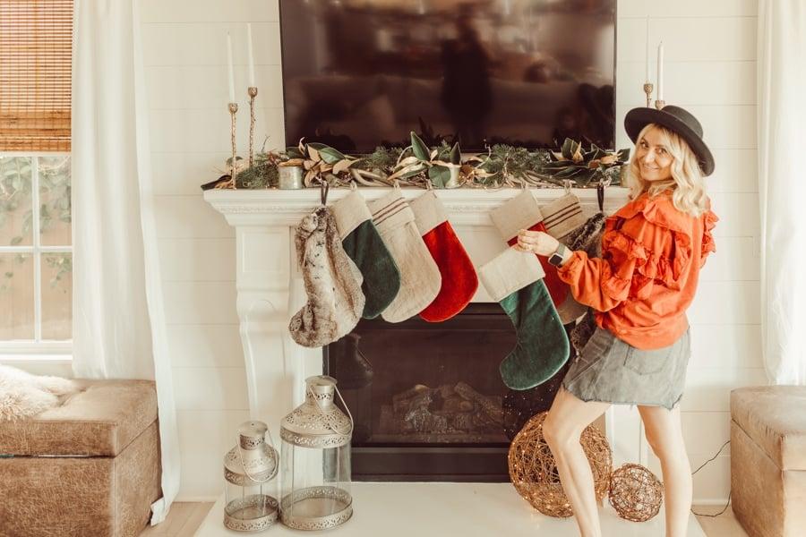 woman hanging christmas stockings
