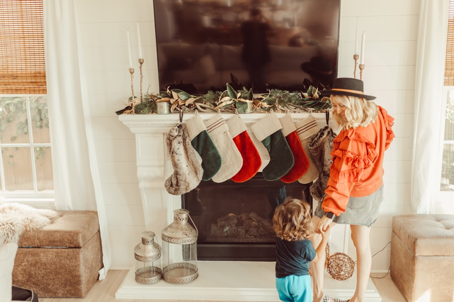 mother and son hanging christmas stockings