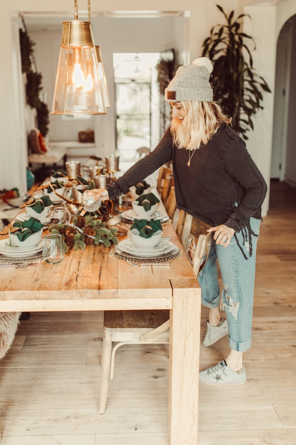 woman decorating christmas dinner table