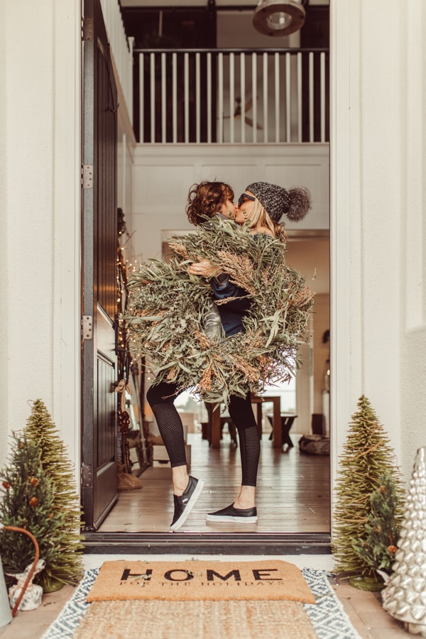 mom and toddler kissing holding christmas wreath