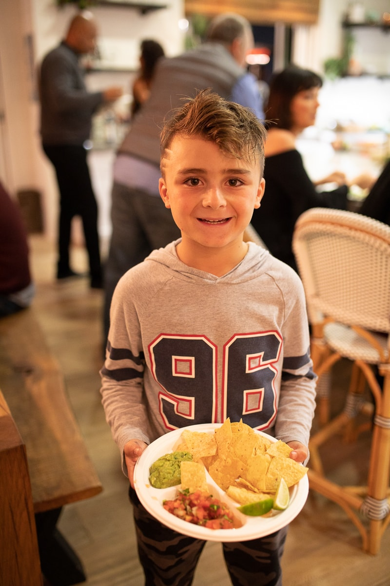 kid with plate of chips and guacamole