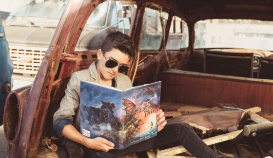 boy reading in old car