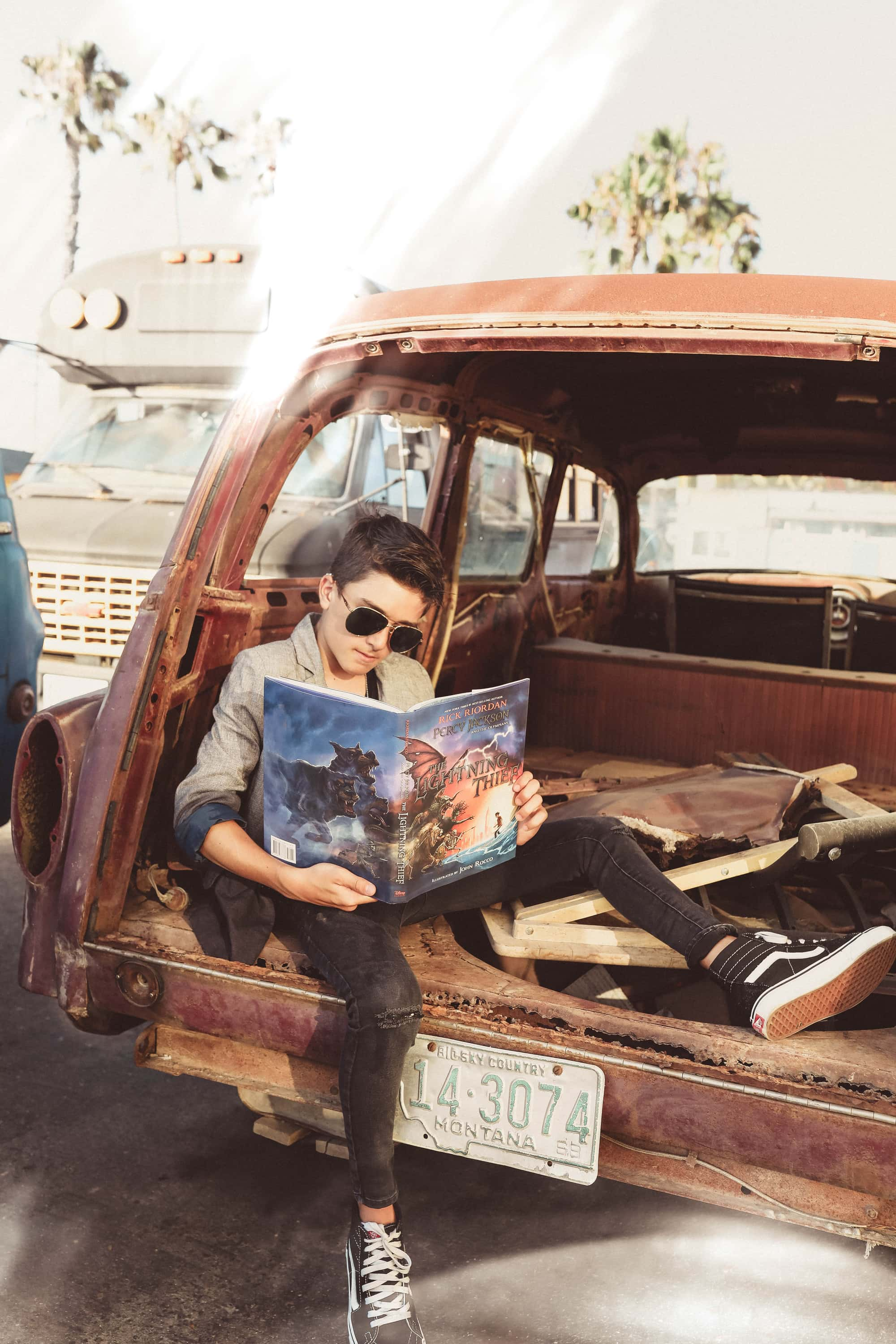 boy reading a book in old car