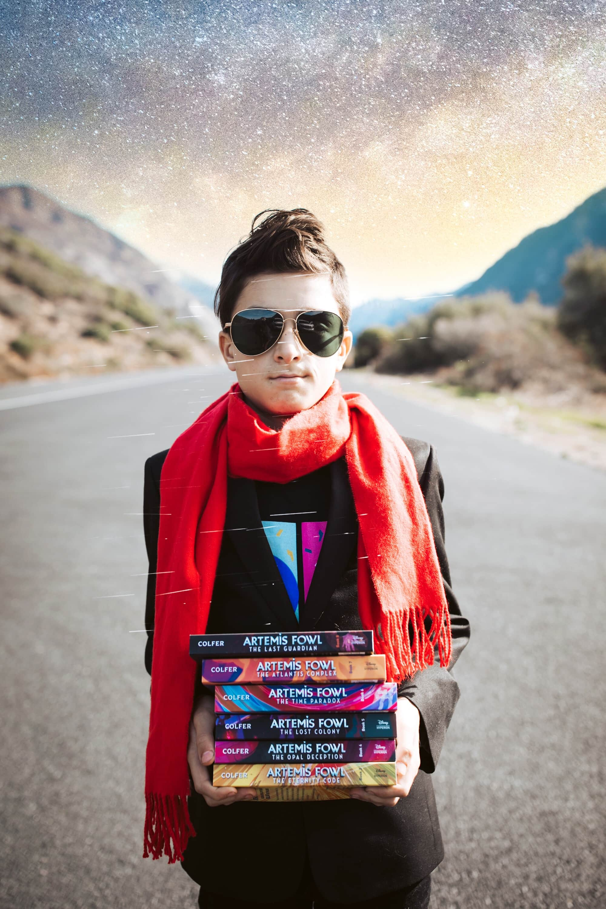 boy holding a stack of books