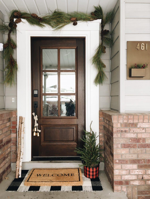 big brown front door with garland