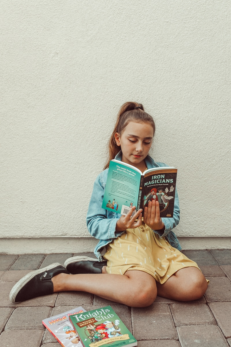 girl reading book outside