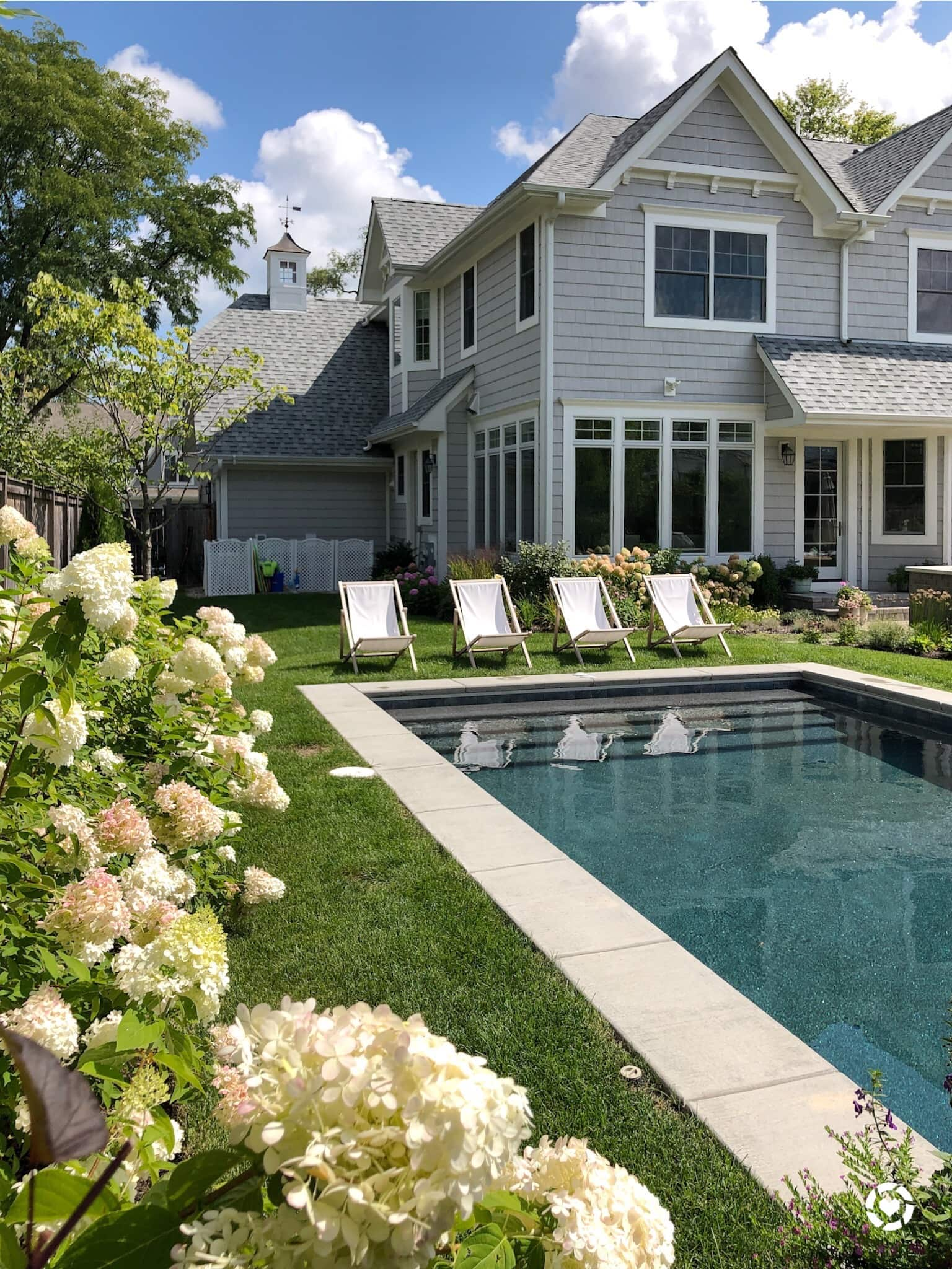 backyard with chairs, flowers and pool