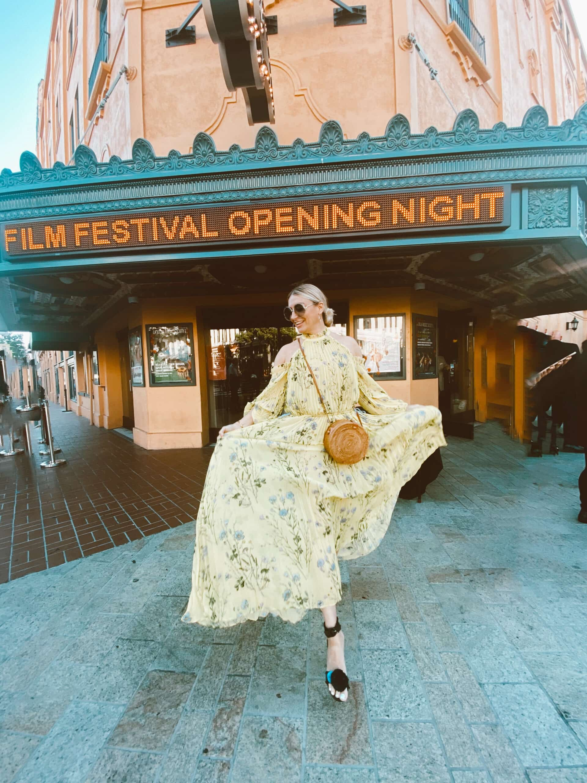 fashionable woman in dress in front of theater