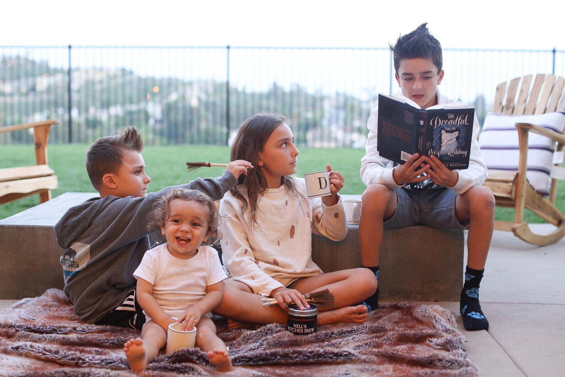 kids reading together in backyard
