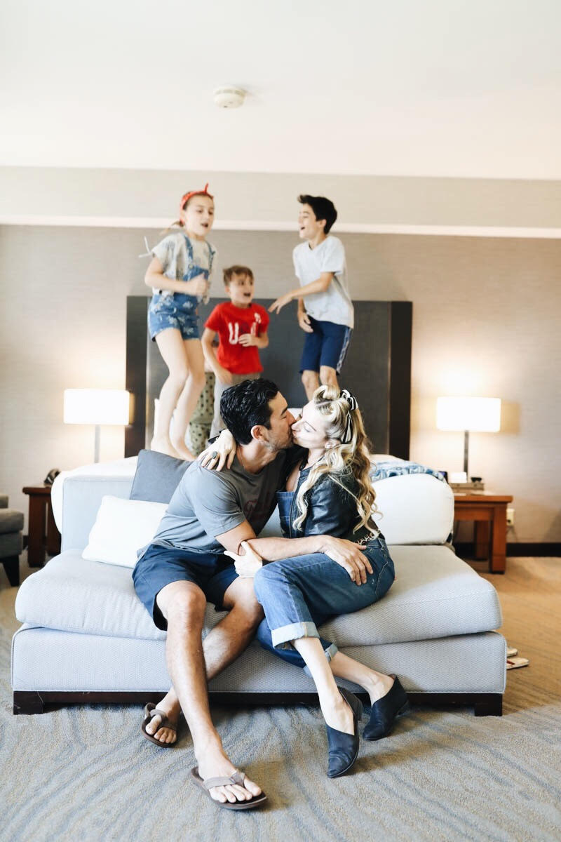 parents kissing while kids jump on bed