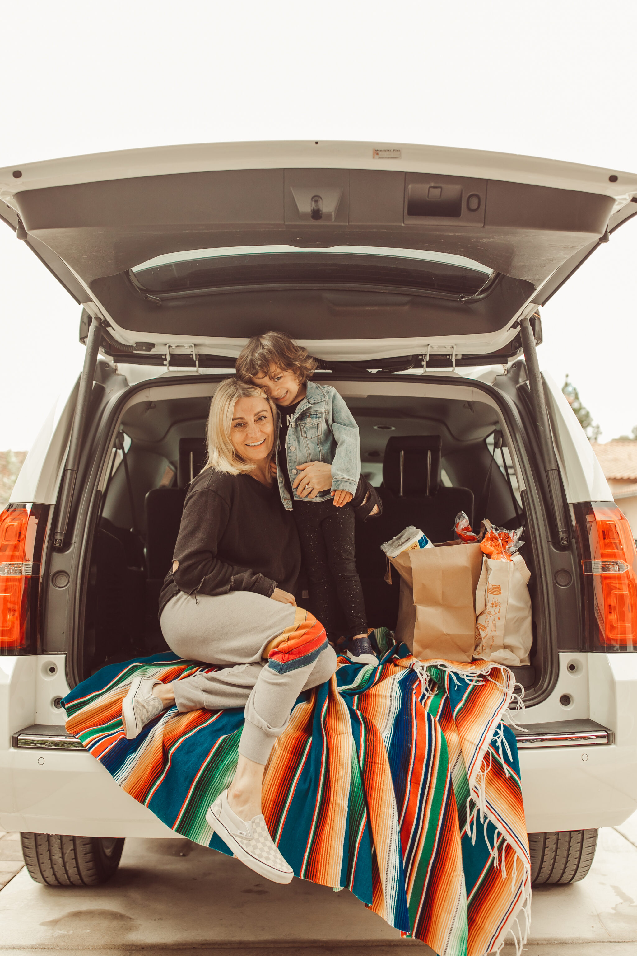 mom and kid with groceries in car