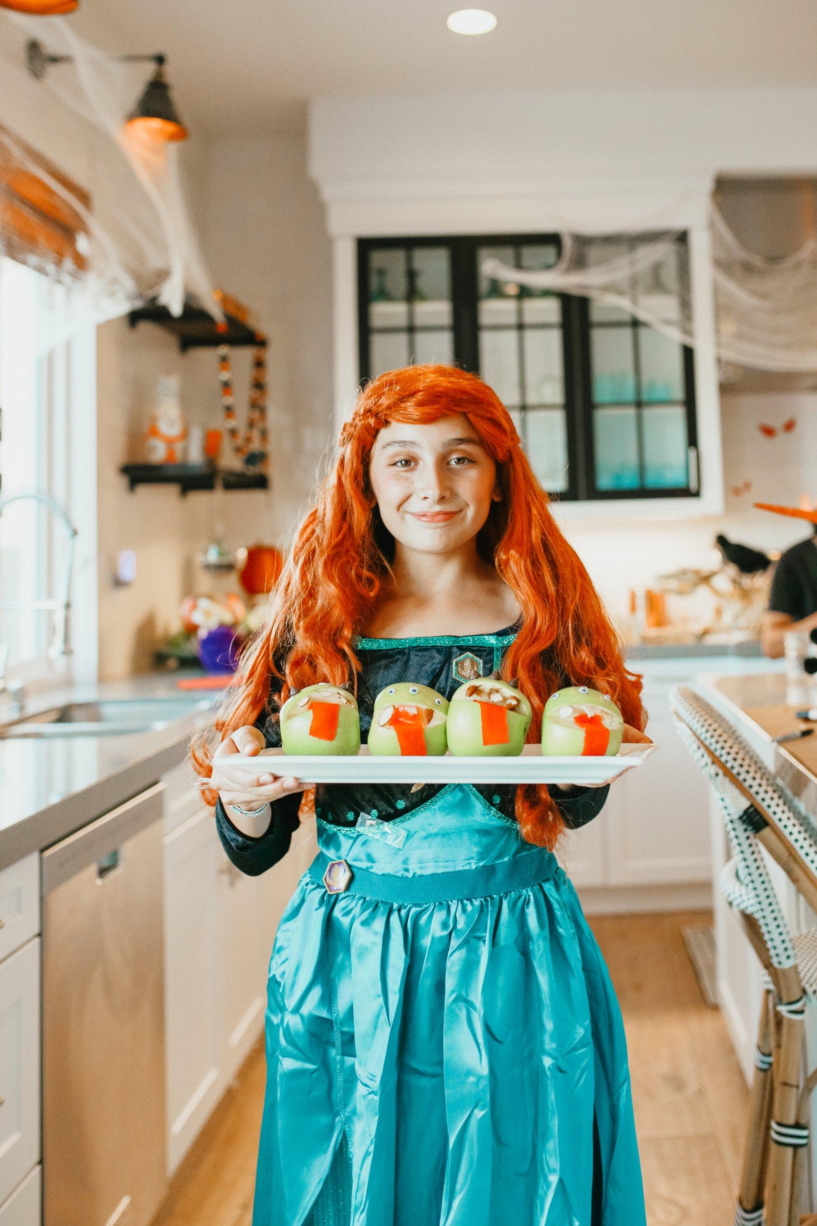 girl in halloween costume holding snacks