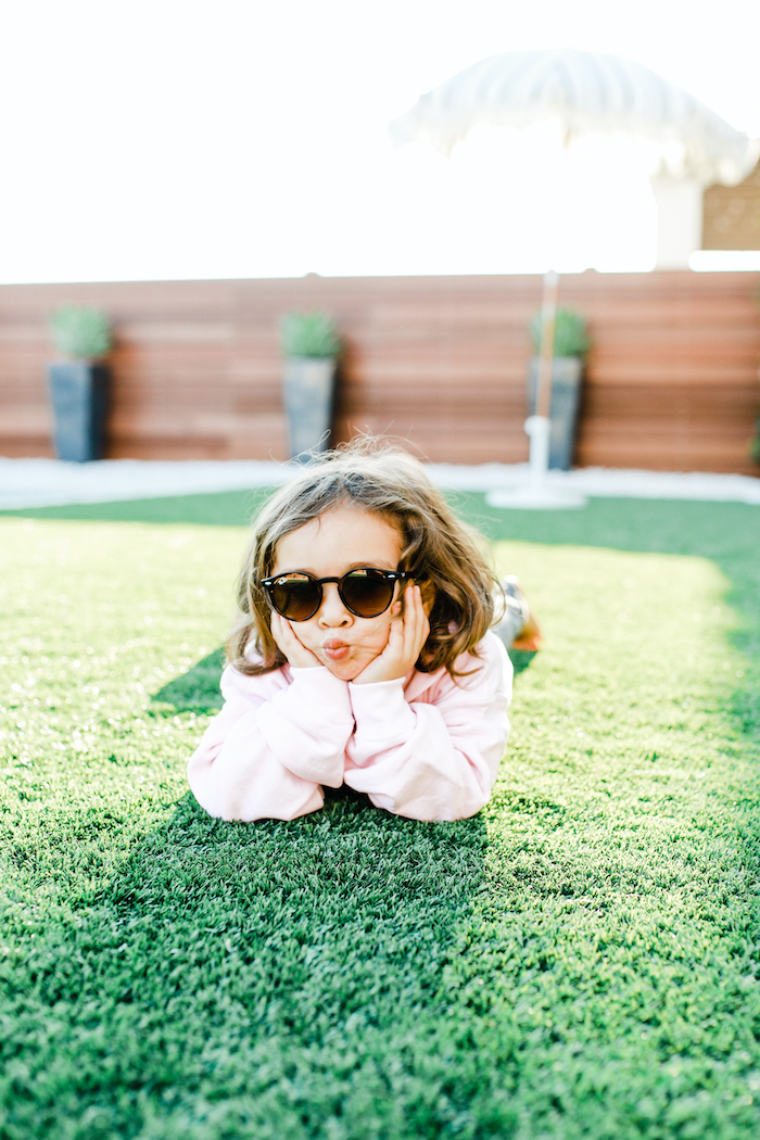 child in sunglasses laying on grass