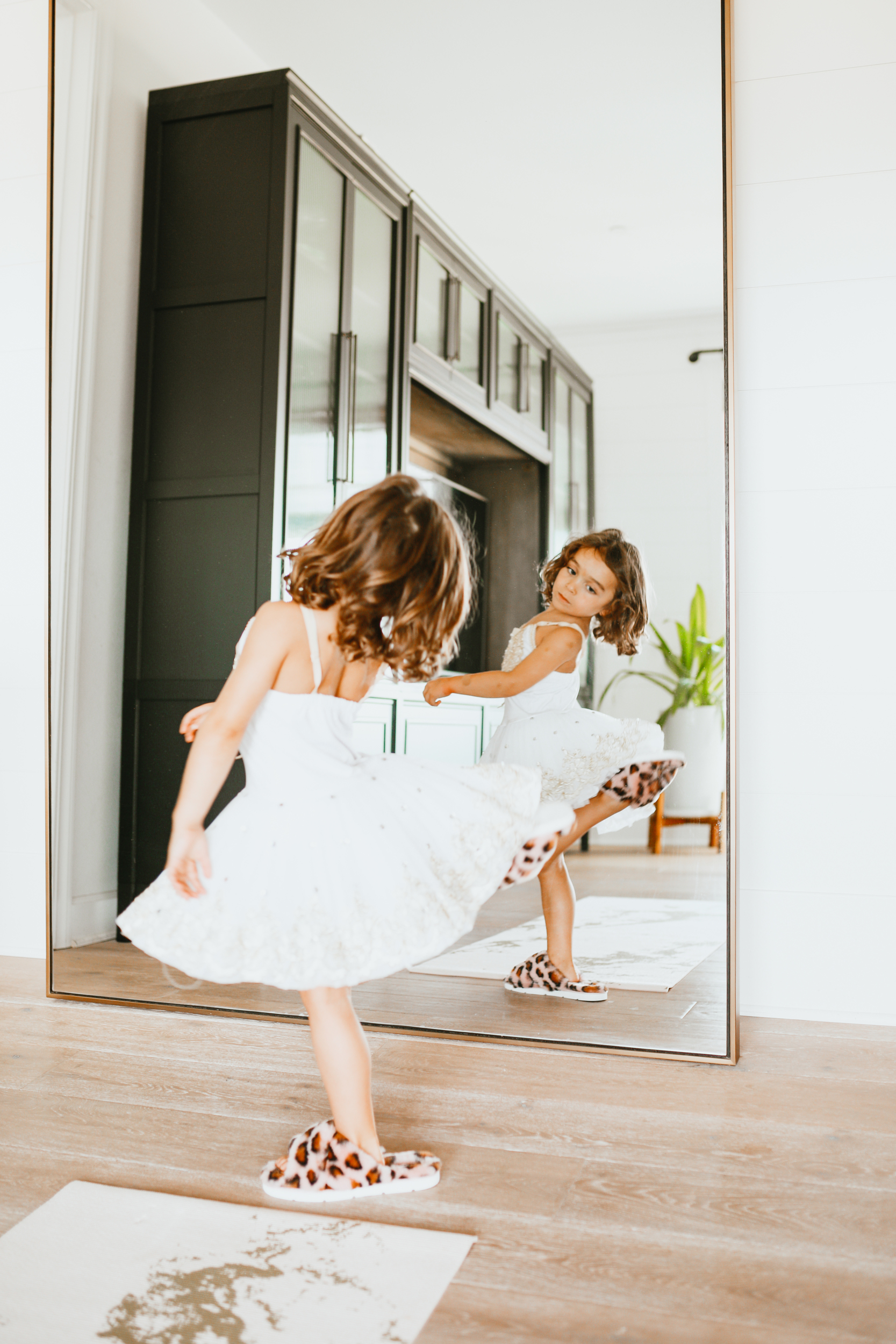 toddler in a dress dancing in front of the mirror