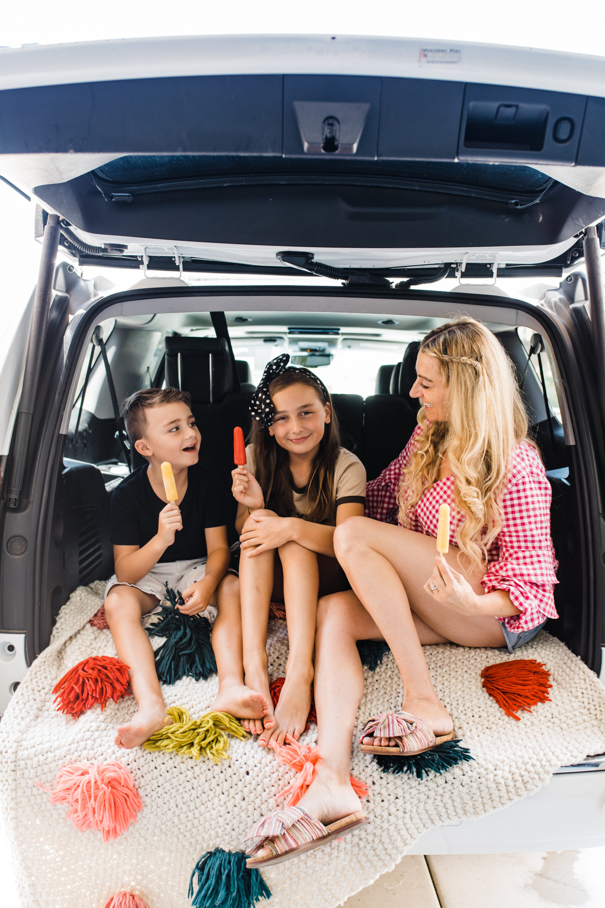kids sitting with mom in back of car