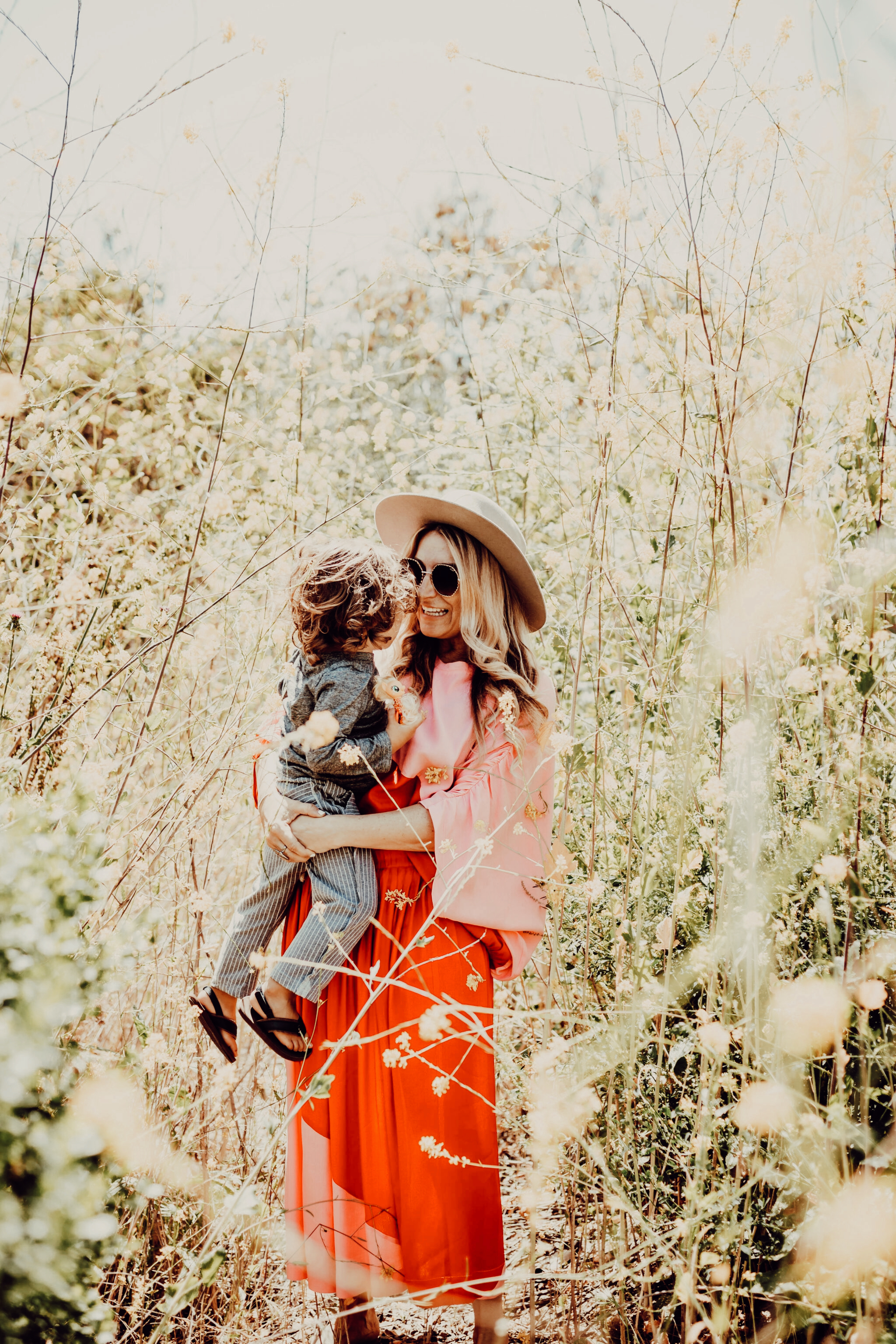 mom and baby standing in a flower field
