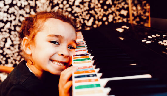 toddler leaning on piano